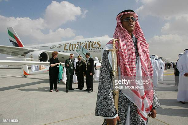An Emirati beduin guard poses in front of an Airbus A380 aircraft the world's biggest passenger jet at the opening of the fiveday Dubai Air Show 20...