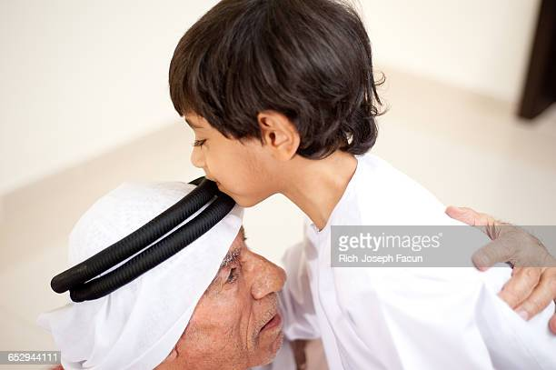 An Emirati Boy shows his respect by kissing his Grandfathers head.