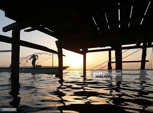 TOPSHOT An Emirati fisherman throws his net on alMirfa beach outside Abu Dhabi on April 30 2016 during the alGharbia Watersports festival / AFP /...