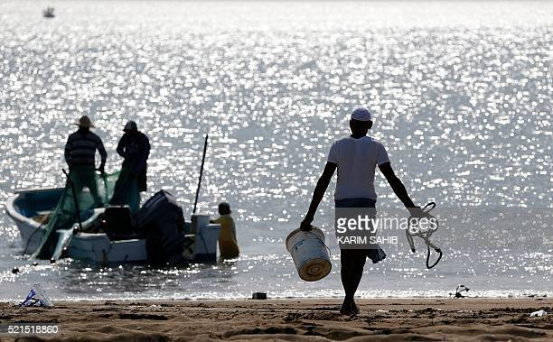An Emirati fisherman walks on a beach as fellow fishermen pull their nets out of the water along the coast of the Gulf of Oman in the Emirate of...