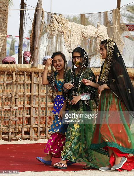 An Emirati girl wears a traditional outfit worn in her village by elderly women during the alGharbia Watersports festival poses near alMirfa beach...