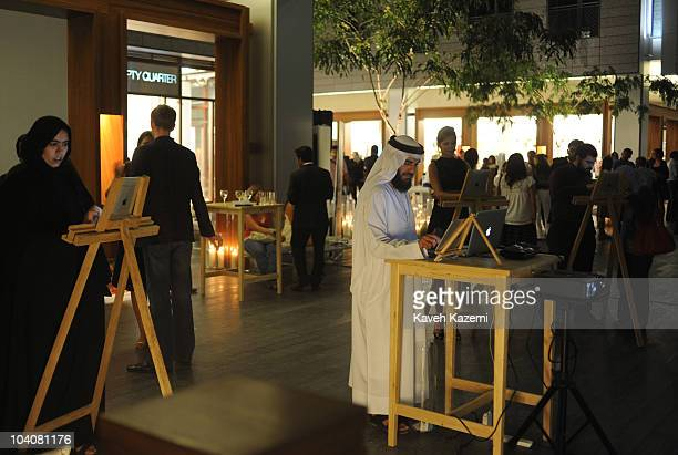 An Emirati man and a woman wearing their traditional costumes make sketches on a touch screen monitor during an arts evening held at galleries and...