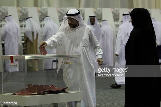 An Emirati man casts his vote in a ballot box at a polling centre at a conventions complex in the Gulf emirate of Dubai on September 24 as voters...