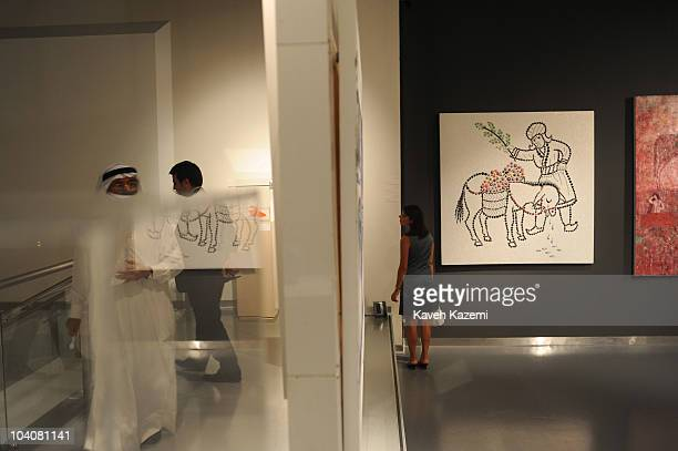 An Emirati man in his traditional costume viewsin an exhibition in Farjam Collection gallery during an arts evening held at galleries and public...