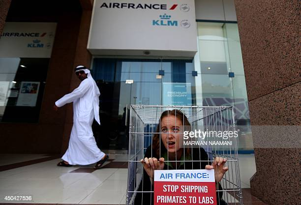 """An Emirati man looks at an activist of the People for Ethical Treatment of Animals imprisoned in tiny cage with a banner reading: """"Air France, Stop..."""