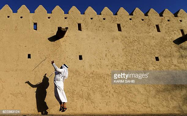 An Emirati man performs a traditional dance in front of the fort on November 11 2016 during the third edition of the Souq alQattara festival in alAin...