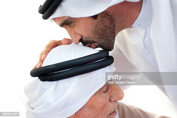 An Emirati man shows his respect by kissing the older mans head.