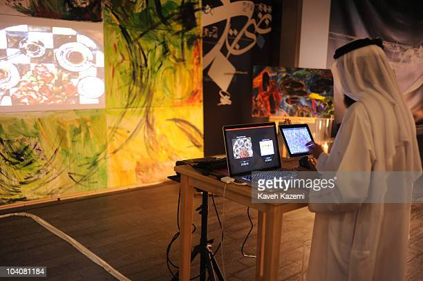 An Emirati man wearing the traditional costume makes sketches on a touch screen monitor during an arts evening held at galleries and public spaces in...