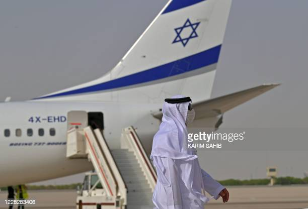 An Emirati official stands near an air-plane of El Al, which carried a US-Israeli delegation to the UAE following a normalisation accord, upon it's...