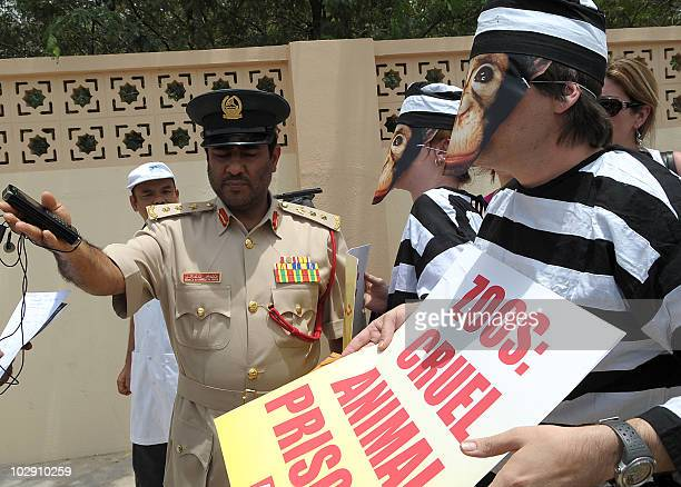 An Emirati policeman talks to activists of the People for the Ethical Treatment of Animals , wearing prison suits and monkey masks, outside the Dubai...