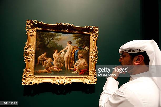 An Emirati visitor looks at 'Venus and Nymphs Bathing' a painting by French artist Louis JeanFrancois Lagrenee that is part of 130 artworks featured...