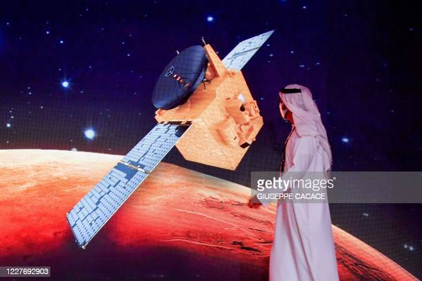 """An Emirati walks past a screen displaying the """"Hope"""" Mars probe at the Mohammed Bin Rashid Space Centre in Dubai on July 19 ahead of it's expected..."""