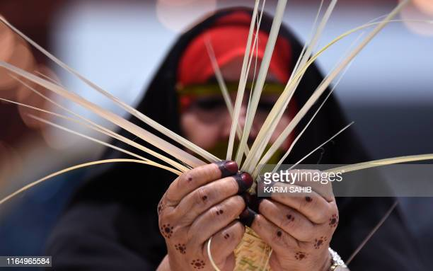 An Emirati woman knits together straw leaves in a display of traditional crafts on the first day of the Abu Dhabi International Hunting and...