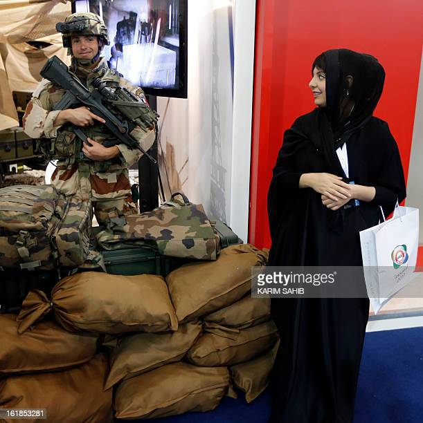 An Emirati woman looks over at a French soldier during the launching of the International Defence Exhibition and Conference at the Abu Dhabi National...