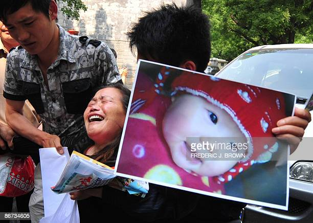 An emotional and grieving Zheng Shuzhen is restrained while holding a portrait of her deceased granddaughter Zhou Mengxin outside the Complaints...