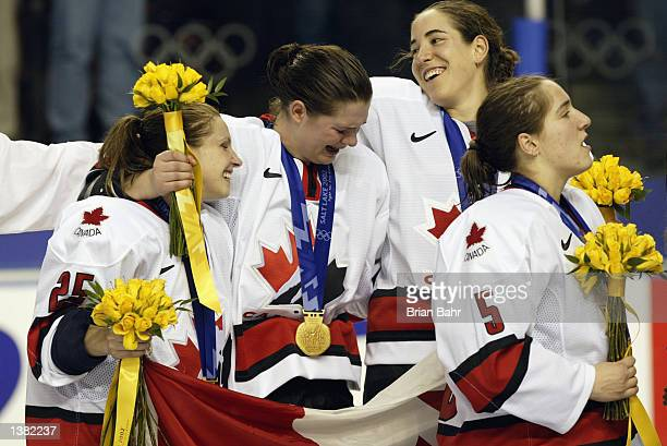 An emotional Canadian team holds up their countries flag as they celebrate their 32 win over the USA during the women's ice hockey gold medal game at...