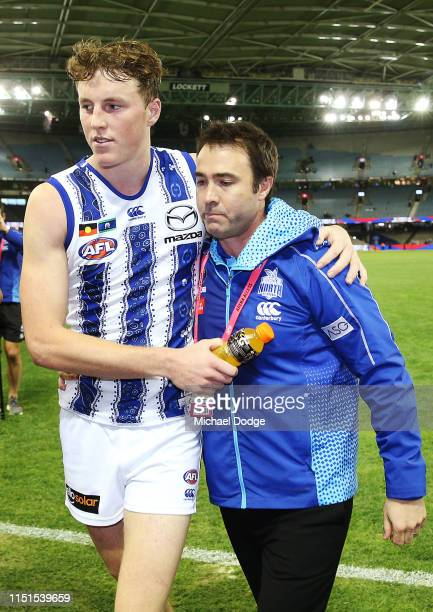 An emotional Kangaroos head coach Brad Scott is hugged after his win by Nick Larkey of the Kangaroos as they walk off during the round 10 AFL match...