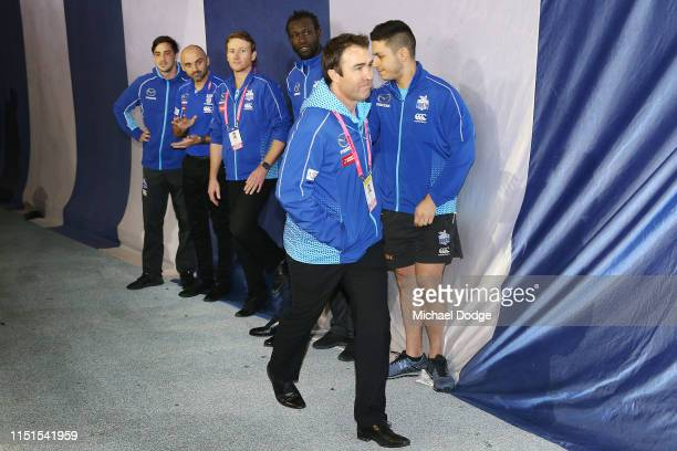 An emotional Kangaroos head coach Brad Scott is seen after his win walking past staff and players during the round 10 AFL match between the Western...