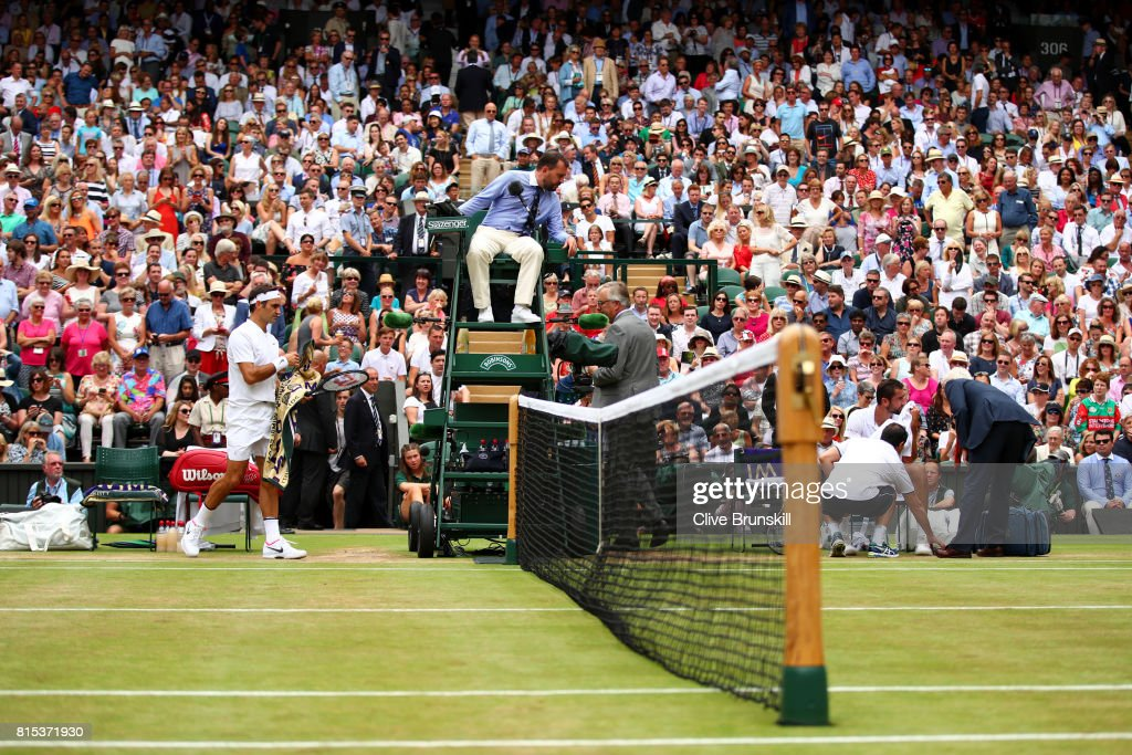 An emotional Marin Cilic of Croatia is given assistance as Roger Federer of Switzerland looks on during the Gentlemen's Singles final on day thirteen of the Wimbledon Lawn Tennis Championships at the All England Lawn Tennis and Croquet Club at Wimbledon on July 16, 2017 in London, England.