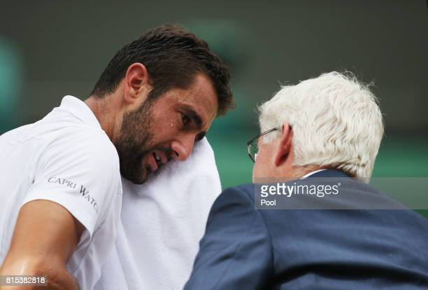 An emotional Marin Cilic of Croatia is given assistance during the Gentlemen's Singles final against Roger Federer of Switzerland on day thirteen of...