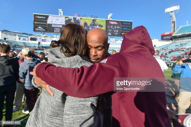 An emotional Mississippi State Bulldogs interim head coach Greg Knox gets a congratulatory hug from his wife and son after the TaxSlayer Bowl game...