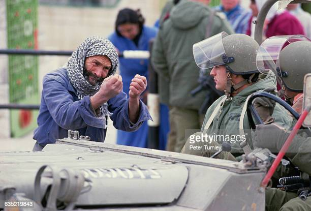 An emotional Palestinian man speaks to two Israeli soldiers during the Intifada