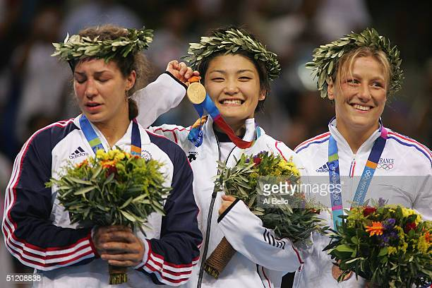 An emotional Sara McMann of the USA silver medalist Kaori Icho of Japan Gold medalist and Lise Legrand of France bronze medalist stand on the podium...