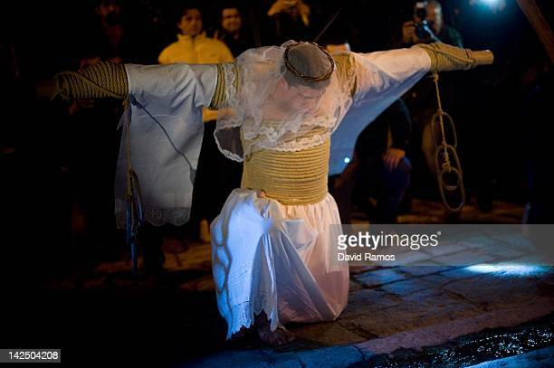 An 'Empalao' penitent prays at one station of the way of the cross or 'Via Crucis' during the procession of the 'Empalaos' on April 6 2012 in...