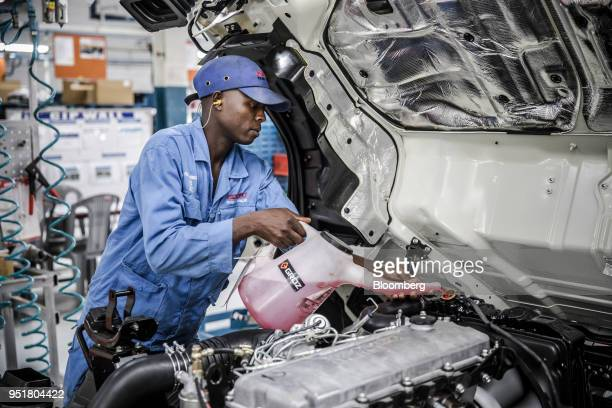 An employee adds antifreeze and coolant solution to the OHC diesel engine of an Isuzu NPR NSeries truck on the assembly line inside the Isuzu East...