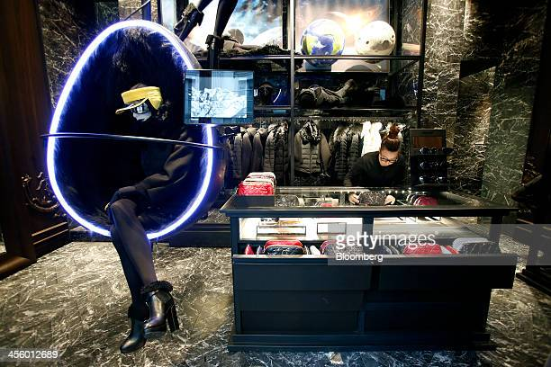 An employee adjusts a display inside a Moncler luxury skiwear store operated by Moncler SpA in Milan Italy on Wednesday Dec 11 2013 Moncler the...