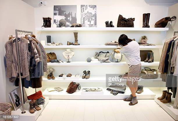 An employee adjusts a garment displayed for sale at the Brunello Cucinelli SpA store in Solomeo near Perugia Italy on Thursday Aug 30 2012 Cucinelli...