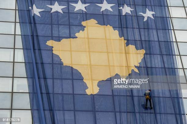 An employee adjusts a giant Kosovo flag on the government building in Pristina on February 14 2018 ahead of the tenth anniversary of Kosovo...