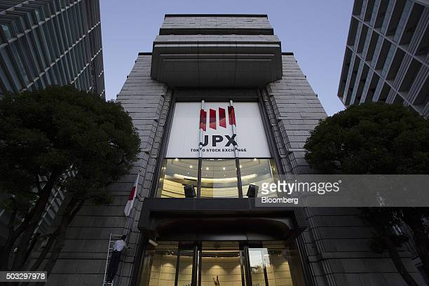 An employee adjusts a Japanese national flag displayed outside the Tokyo Stock Exchange operated by Japan Exchange Group Inc in Tokyo Japan Monday...