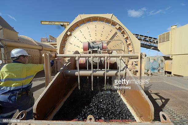 An employee adjusts a lever on the side of a sag mill as ore is washed while passing through a vibration rack at Saracen Mineral Holdings Ltd's...