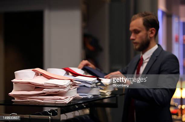 An employee adjusts a shirt and tie display at the Gieves Hawkes store owned by Trinity Ltd on Saville Row in London UK on Tuesday Aug 7 2012 UK...