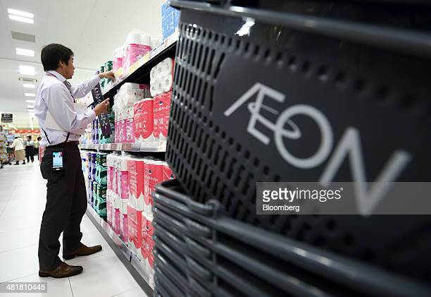 An employee adjusts a sign in front of a display of toilet rolls at an Aeon Co supermarket in Chiba Japan on Tuesday April 1 2014 Japan's economy...