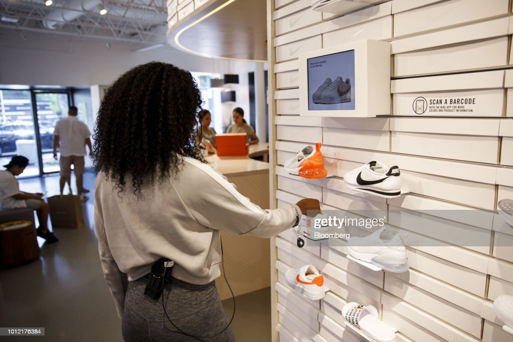comprare popolare prezzi al dettaglio imbattuto x An employee adjusts a sneaker displayed for sale at the Nike by ...