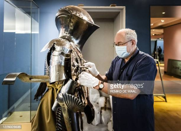 """An employee adjusts a suit of German tournament armour from around 1500, for the exhibition """"Romanovs under the spell of the knights"""" at The..."""