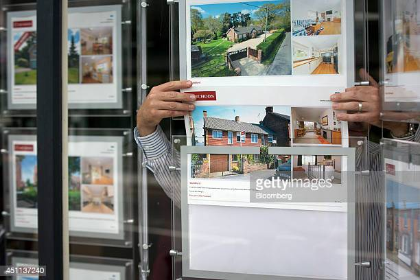 An employee adjusts an information leaflet for a residential property in the window display of an estate agents in this arranged photograph taken in...