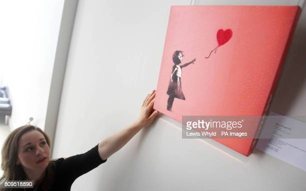 An employee adjusts Banksy's Balloon Girl during a photocall for highlights from Bonhams' Urban Art Sale on September 21 in London