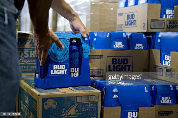 An employee adjusts bottles of Bud Light brand beer at an Anheuser-Busch InBev NV facility during a campaign stop by Senator Tim Kaine, a Democrat...
