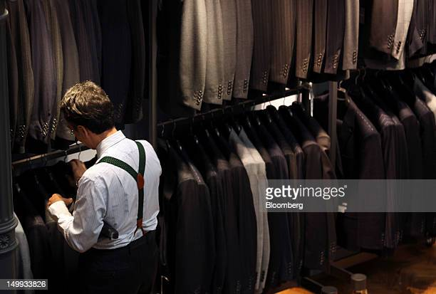 An employee adjusts the suit display at the Gieves Hawkes store owned by Trinity Ltd on Saville Row in London UK on Tuesday Aug 7 2012 UK retail...