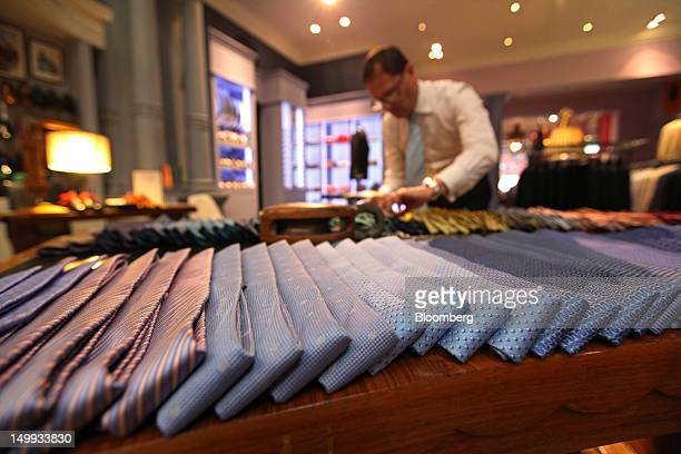 An employee adjusts the tie display at the Gieves Hawkes store owned by Trinity Ltd on Saville Row in London UK on Tuesday Aug 7 2012 UK retail sales...