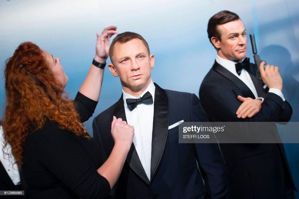 An Employee Adjusts Wax Figures Of James Bond Actors Daniel