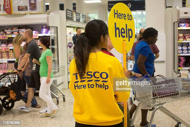 An employee advertises her services with a 'Help' lollipop inside a Tesco Plc store in Watford UK on Thursday Aug 8 2013 UK grocery sales rose...