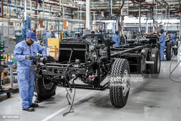 An employee affixes electronics to the chassis of an Isuzu truck on the assembly line inside the Isuzu East Africa Ltd plant in Nairobi Kenya on...