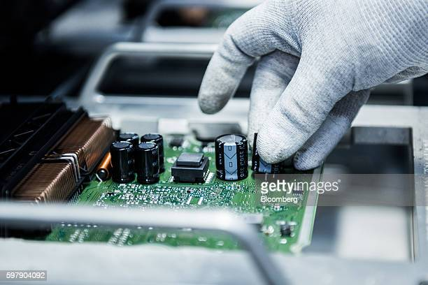 An employee affixes parts to an engine control module on the assembly line inside the Robert Bosch GmbH manufacturing plant in Hatvan Hungary on...