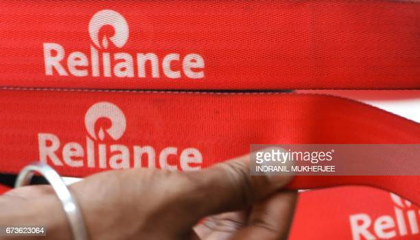 An employee aligns a retractable belt with the Reliance logo at a Reliance Digital store in Mumbai on April 21 2017 Indian conglomerate Reliance...