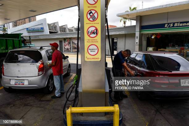 An employee and a customer pump fuel at a gas station in Caracas on July 30 2018 Venezuelan President Nicolas Maduro announced fuel price regulations...
