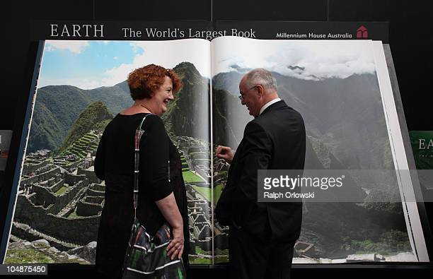 An employee and a visitor stand in front of the world's largest book at the Millenium House publishers stand during the Frankfurt Book Fair 2010 on...